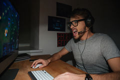 Excited gamer in glasses and earphones playing computer game Stock Photo