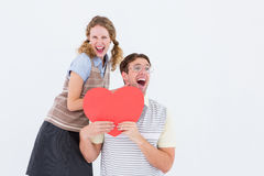 Excited geeky hipster couple with heart card Stock Images