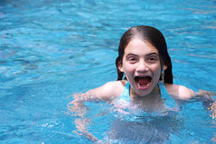 Excited Girl. Young brunette girl with an excited expression swimming in a tropical pool Royalty Free Stock Photo