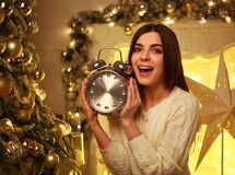 Excited girl with alarm clock at home in Christmas decorations Stock Photo