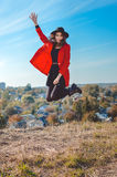Excited girl in black hat jumping on autumn Royalty Free Stock Image