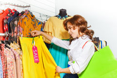 Excited girl chooses yellow skirt during sale Stock Photo