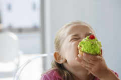 Excited Girl Eating Cupcake Stock Photo