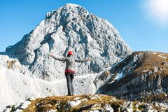Excited girl exercising with orange hat looking to a mountain peak on a nice autumn sunny day stock photo