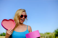 Excited girl in fancy sunglasses opening pink Royalty Free Stock Photography