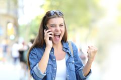 Excited girl having a phone conversation in the street. Excited girl having a positive mobile phone conversation in the street Stock Photos