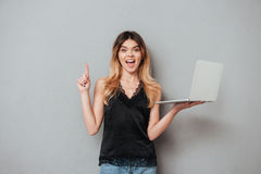 Excited girl holding laptop and pointing finger up at copyspace. Portrait of a happy excited girl holding laptop and pointing finger up at copy space over grey royalty free stock photos