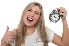 Excited girl holding old fashioned alarm clock Stock Image