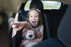 Excited girl holding teddy bear while gesturing in car. Portrait of excited girl holding teddy bear while gesturing in car Stock Images