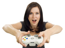 Excited girl holding video game controller. Girl holds a video game controller with her mouth open, exclaiming Stock Photo