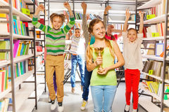 Excited girl holds cup and kids jump behind. Excited girl holds golden cup and other kids jumping behind in the library Royalty Free Stock Image