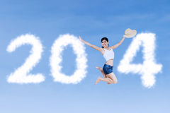 Excited girl jumping announce Happy New year 2014. Excited girl jumping announce Happy New year on blue sky Royalty Free Stock Image