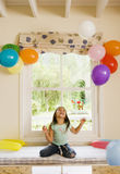 Excited girl (4-6) kneeling on window seat at home, looking up at party balloons attached to wall, smiling, front view Royalty Free Stock Image