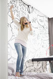 Excited girl listening music while singing into hairbrush at home Stock Image