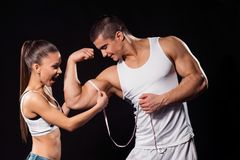 Excited girl measuring bodybuilder`s bicep. stock photography