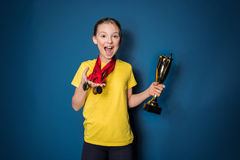 Excited girl with medals and trophy cup Stock Photo