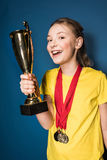 Excited girl with medals and trophy cup Royalty Free Stock Photos