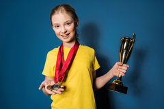 Excited girl with medals and trophy cup Royalty Free Stock Images