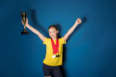 Excited girl with medals and trophy cup. On blue Royalty Free Stock Images