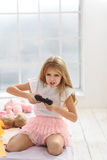 Excited girl playing game console. I must win. Full of enthusiasm female child playing playstation. She is holding a joystick in her hands Royalty Free Stock Photo