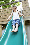 Excited Girl Playing On Slide In Park Royalty Free Stock Images