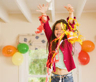 Excited girl (4-6) playing with streamers at birthday party, arms up, smiling, front view, portrait Stock Images