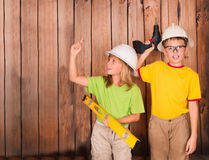 Excited girl pointing a great idea. Construction and renovation. Concept. Happy children in hardhats with tools on wooden background with copyspace Royalty Free Stock Image
