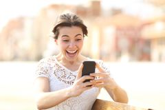 Excited girl reading amazing news on a phone royalty free stock images