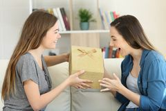 Excited girl receiving a gift from a freind. Sitting on a couch in the living room at home Royalty Free Stock Image