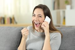 Excited girl receiving good news during a phone call. Sitting on a couch in the living room at home Royalty Free Stock Images