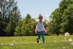Excited girl running in park. On a sunny day Royalty Free Stock Image