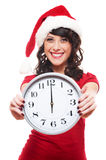 Excited girl with santa hat holding clock Royalty Free Stock Photography