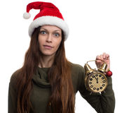 Excited girl with santa hat holding clock. Stock Photos