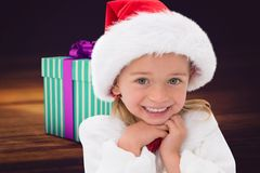 Excited girl in santa hat smiling at camera. During christmas time Royalty Free Stock Photography