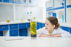 Excited girl scientist looking at experimental tube in lab Stock Images