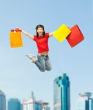 Excited girl with shopping bags. Shopping and movement concept - happy girl with shopping bags Royalty Free Stock Photos