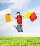 Excited girl with shopping bags. Shopping and movement concept - happy girl with shopping bags Stock Images