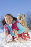 Excited girl sledding down snowy hill on sled Royalty Free Stock Photos