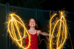 Excited Girl With Sparklers. A young girl with a sparkler in each hand grins with excitement at the camera as she tries to pull her head away from the fire Stock Photo