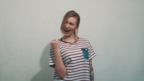 Excited girl in striped shirt with tattoos victorious pose and scream