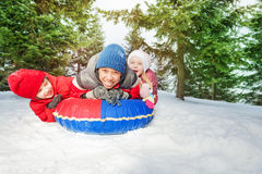 Excited girl and two boys on snow tube in winter Stock Photo