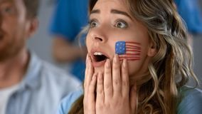 Excited girl watching American football, worrying about defeat of favorite team. Stock photo stock photos