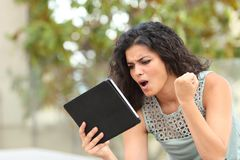 Excited girl watching media content on a tablet in a park royalty free stock photography
