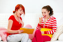 Excited girlfriends reading letter with good news Stock Photos