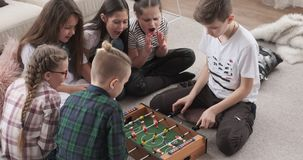 Excited girls cheering for brothers playing foosball. Excited little girls cheering for boys playing foosball at home stock footage