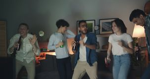 Excited girls and guys dancing at home party holding bottles with drinks stock footage