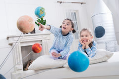 Excited girls looking at planets models. At home Stock Photo