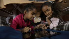 Excited girls playing online games on touchpad. Portrait of smart african american kids using digital tablet pc in domestic interior. Adorable mixed race little stock video
