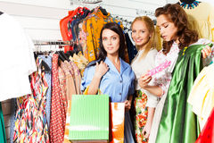 Excited girls with shopping bags choose clothes Stock Images