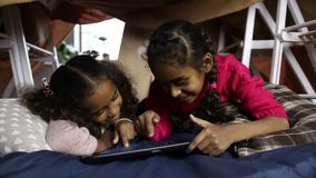 Excited girls watching funny video on tablet. Joyful little mixed race sisters watching funny video on digital tablet while lying down in cubby house made of stock video footage